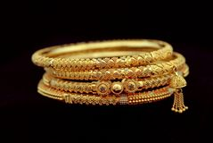 Gold. 4 gold bangles in black background Stock Photography