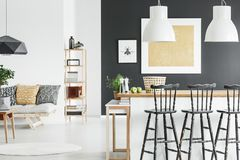 Gold accents in contrast interior. Gold accent in contrast color interior with white lamps above wooden countertop and black bar stools stock photography