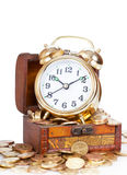 Gold alarm clock. Lay on money in a wooden chest stock photography