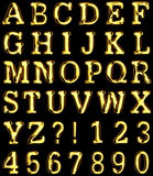 Gold alphabet on black background.  Added clipping path Stock Photography