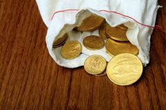 Gold american coins. On wooden table in fabric pouch royalty free stock image