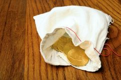 Gold american coins. On wooden table, in fabric pouch stock image