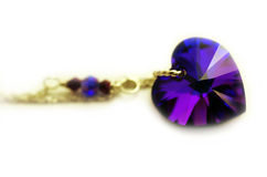 Gold Amethyst Heart Necklace. Macro close up of a gold necklace with a beautiful blue and purple amethyst crystal heart royalty free stock photo