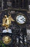 Gold Angel On ein Kirchen-Tor mit der Kirchen-Uhr im Hintergrund Stockbild