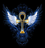 Gold ankh. With white wings on a dark blue patterned background Stock Image