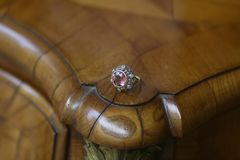 Antique pink gemstone and diamonds ring. Gold antiques dusty rose gemstone and brilliant cut diamonds ring on a baroque wooden cabinet Stock Images