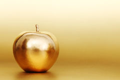Gold apple. On gold background Royalty Free Stock Photography
