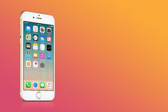 Gold Apple iPhone 7 with iOS 10 on the screen on pink gradient background with copy space Stock Images