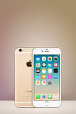 Gold Apple iPhone 7 with iOS 10 on the screen on vertical gradient background with copy space Stock Images
