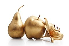 Gold apple, pear and flower. On white royalty free stock image