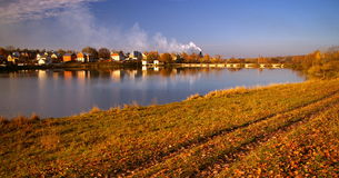 Gold Autumn - field, houses on a bank of the lake Royalty Free Stock Photo