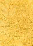 Gold background for a design. The compressed silk of gold color laying on a table Stock Photos