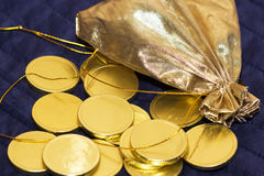 Gold bag with gold chocolate coins. Bag of gold chocolate coins on a blue background Stock Photos