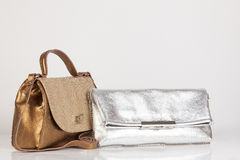 Gold bag meets silver clutch Stock Image