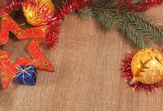 Gold bal, red starl and blue gift with coniferous branch on wood royalty free stock photos