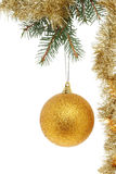 Gold ball and tinsel. Gold Christmas ball decoration and tinsel hanging from a branch of a Christmas tree against a white background Royalty Free Stock Image