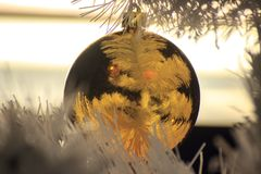 Gold ball on a white Christmas tree, decorations for the new year and Christmas. Cozy home, preparing for fun. Background for stock image