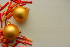Gold balls as new year and Christmas decoration with bright colorful sticks on white background with copy space. Coziness and celebration of winter holidays Stock Images