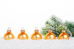 Gold balls in snow on white Stock Photo