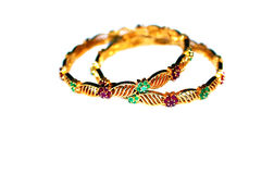 Gold bangles with green and pink rubies Royalty Free Stock Images