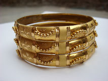 Gold bangles on white background. Picture of gold bangles on white background Royalty Free Stock Photography