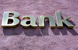 Gold Bank. Sign on red stucco facade Stock Images