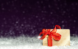 Gold bank card with red tape on a background of falling snow. Gold bank card with with a bow on a background of falling snow royalty free stock photos