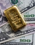 Gold bar against the background of dollar bills Royalty Free Stock Image