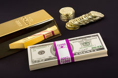 Gold bar and coins on black Royalty Free Stock Photos
