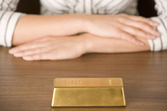 Gold Bar On Desk. With Unrecognizable Woman Royalty Free Stock Image