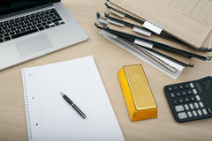 A gold bar on desk Stock Images