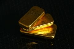 Gold bar on gross background scene. The gold bars put on the dark and gross surface background represent the business and finance concept related idea stock photos