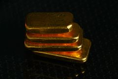 Gold bar on gross background scene. The gold bars put on the dark and gross surface background represent the business and finance concept related idea stock photography