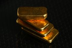Gold bar on gross background scene. The gold bars put on the dark and gross surface background represent the business and finance concept related idea stock image