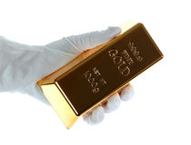 Gold bar in hand with white glove Royalty Free Stock Photos