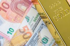 Gold bar ingot bullion against the background of dollar and euro bills.  royalty free stock images