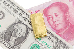 Gold bar over the US dollar bill and Chinese yuan banknote on wh Stock Photos