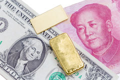 Gold bar over the US dollar bill and Chinese yuan banknote on wh. Ite background, economy finance concept Stock Image