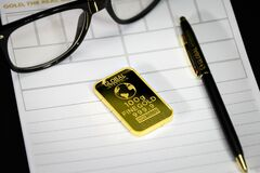 Gold bar with pen and eyeglasses