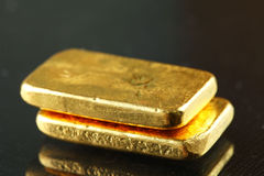 Gold bar put on the dark background. Royalty Free Stock Images