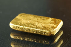 Gold bar put on the dark background. Royalty Free Stock Image