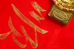 Gold bar scene. The gold bar put on the red color paper with chinese letter written from chinese brush as a background  represent the wishes concept related Royalty Free Stock Images