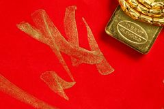 Gold bar scene. The gold bar put on the red color paper with chinese letter written from chinese brush as a background  represent the wishes concept related Stock Images