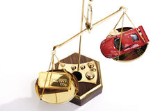 Gold bar and toy car on scale Royalty Free Stock Photos