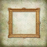 Gold baroque empty frame on Victorian wallpaper. Vintage frame on faded grunge stylized texture stock photos