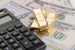 Gold bars or bullion ingot on pile of money US dollar bills with. Calculator, success investment or financial wealth calculation concept Stock Photos