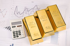 Gold bars and calc closeup on white background Royalty Free Stock Photos