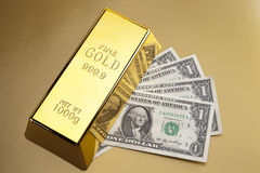 Gold bars closeup and dollars Royalty Free Stock Photos