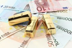 Gold bars and Euro. Three gold bars on many colorful euro notes Stock Image