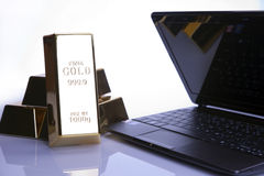 Gold bars and laptop Stock Images